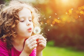 a little girl blows on a dandelion