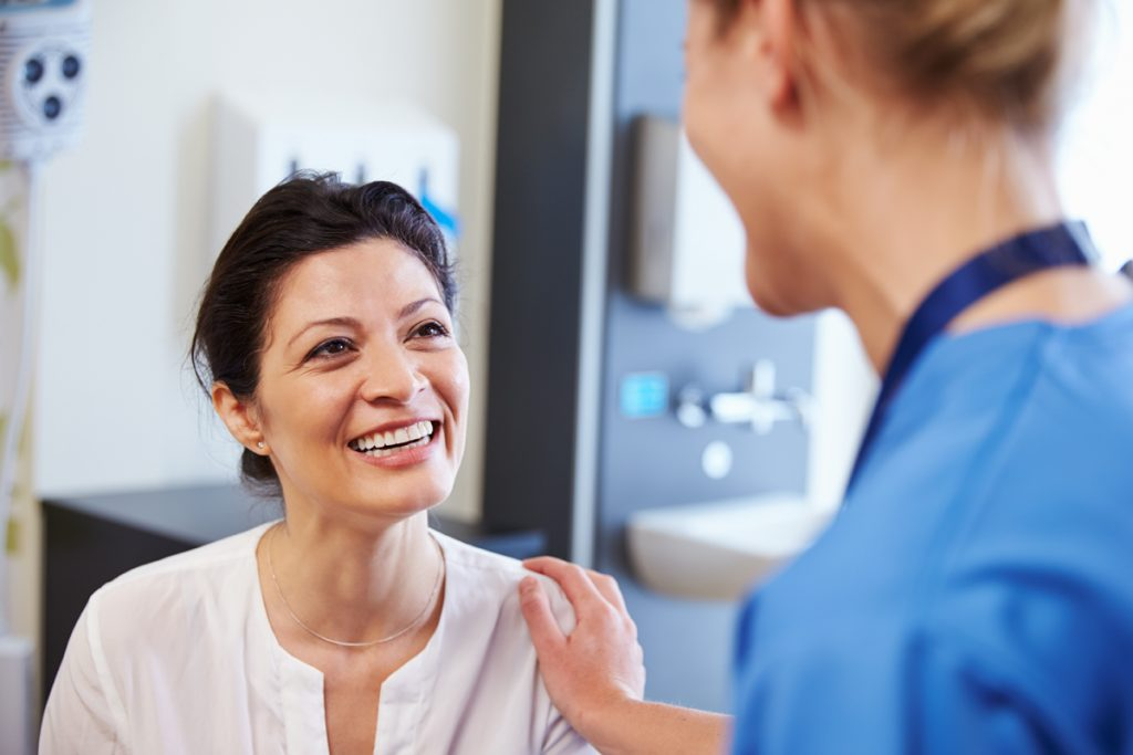 Female Patient Being Reassured By Doctor In Hospital Room for health screenings