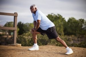 An attractive senior black man exercises outdoors with various muscle stretches