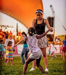 A young girl and a teen dance in the foreground at Central Park in Denver.